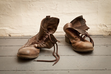 Worn out old boots thrown away on to the floor