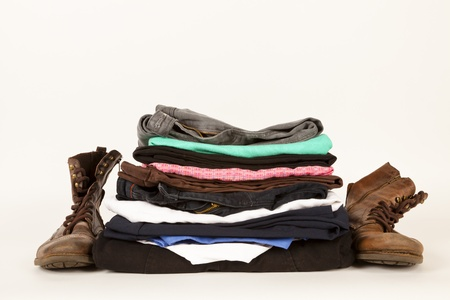Pair of boots and a pile of old clothes for the charity shop or a jumble sale Stock Photo