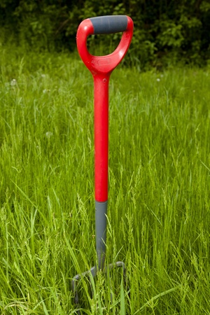 Garden fork in an overgrown garden or allotment with a lot of hard work ahead photo