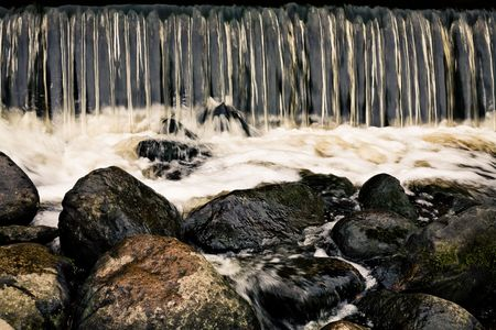 falling tide: Small waterfall and a pebble Stock Photo