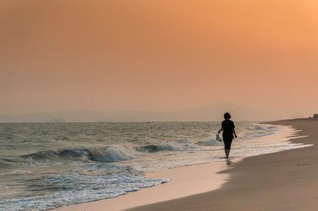 해변에서 혼자 걷는 여자