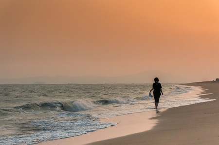 walking alone: mujer caminando sola en la playa