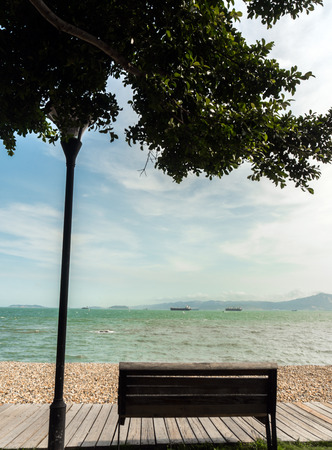 the silence of the world: wooden bench at sunny day seaside