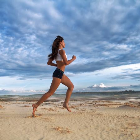 Laufende barfuss Frau. Weiblicher Läufer, der während des Trainings im Freien auf Sand am Abend rüttelt. Schönes Eignungsmodell draußen.