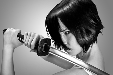 Anime stylized brunettewith short hair watching with stern look holding a katana sword with two hands Archivio Fotografico