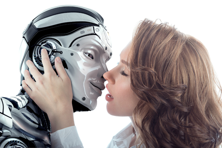 A beautiful woman kissing male robot with love. Two faces very close to each other. Relationship between artificial cyborg and real girl. Closeup portrait of futuristic couple communication.