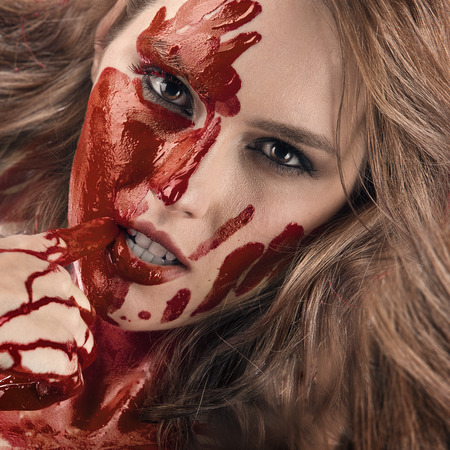 assasin: Closeup portrait of a beautiful female model with red blood dripping on hand. Red hair killer touching her face with arm in a dribble of blood. Stock Photo