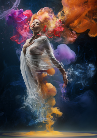 Fantasy fashion model inside colorful clouds. Water paint spreading underwater. Fantastic shapes in deep space.