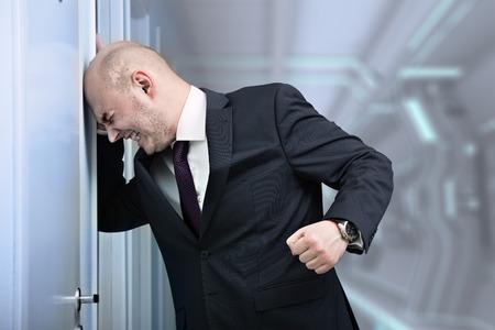 Businessman in a fury banging head against wall 版權商用圖片