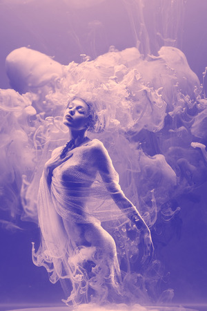 Fantasy fashion model inside ultraviolet clouds. Paint spreading underwater. Abstract shapes in space.