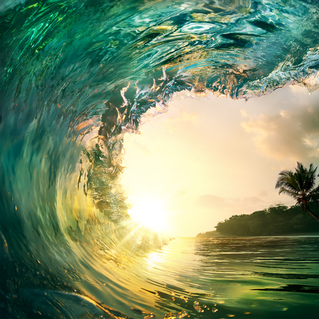 Tropical sunset background. Beautiful colorful ocean wave crashing closing near sand beach with palm tree