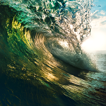 breaking colorful ocean wave falling down at sunset time
