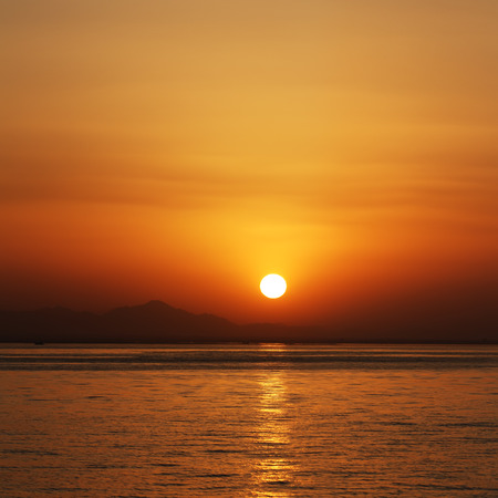 orange sunset at the sea with mountains silhouettes on horizont