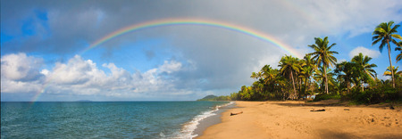 palmtrees: A Tropical Pacific oceanscape with palmtrees, rainbow, clouds