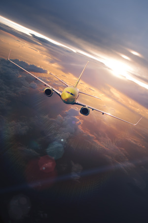 air plane: airplane flying through beautiful clouds at the sunset time with sunlight Stock Photo