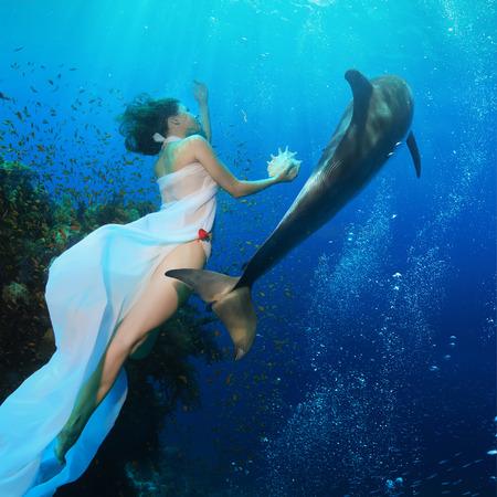아름 다운 인 어 산호초 근처 야생 돌고래와 깊고 푸른 바다에서 수영하는 조개를 들고. 수 중 사진입니다. 스톡 콘텐츠