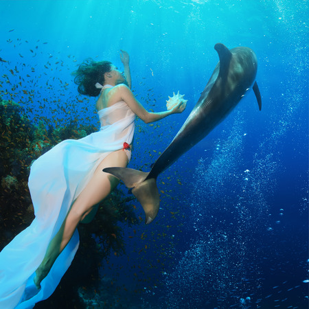 Beautiful mermaid holding seashell swimming in deep blue ocean with wild dolphin near coral reef. Underwater photo.