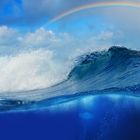 shorebreak: ocean view cloudy sky with colourful rainbow and breaking surfing wave splitted to two parts by waterline Stock Photo