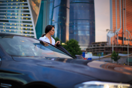 time drive: Business female going to drive a luxury car after work at evening time. Focus on her face and office buildings on background in a sunset light Stock Photo