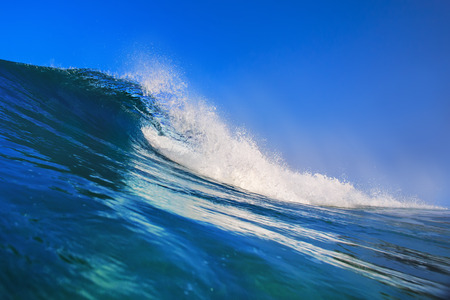oahu: Shorebreak surfing tube wave. Pipeline in daylight with light of sun. Green Blue Ocean Water. Surfing template design with nobody. White splashes and ocean foam. Sky with no clouds. Surfing Rip Curl. Stock Photo