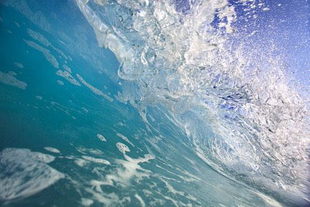 shorebreak: Shorebreak surfing tube wave. Pipeline in daylight with light of sun. Green Blue Ocean Water. Surfing template design with nobody. White splashes and ocean foam. Sky with no clouds. Surfing Rip Curl. Stock Photo