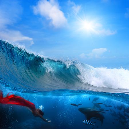 깨는 바다 서핑 파도 아래 공기 방울에 둘러싸여 야생 상어와 다이빙하는 아름 다운 인 어 공주
