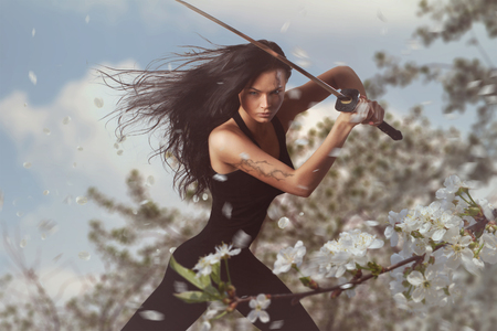 봄 꽃 환경에서 katana 칼을 가진 아름다운 갈색 머리