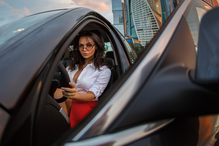 Business woman in a black car on drivers seat after hardworking day. A Brunette Lady sitting in a luxury vehicle looking from open door. Archivio Fotografico
