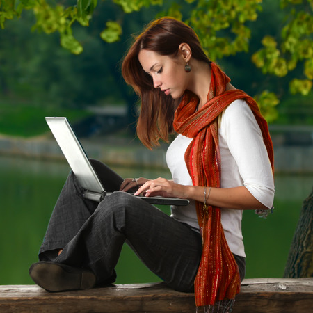 neckerchief: a cute student girl in red neckerchief working with laptop outdoor summer time close to pond Stock Photo