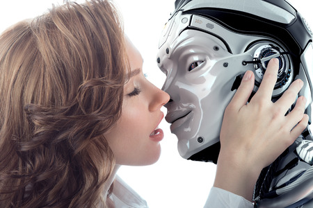 A beautiful woman kissing male robot with love. Two faces very close to each other. Relationship between artificial cyborg and real girl. Closeup portrait of futuristic couple. Archivio Fotografico
