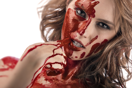 assasin: Closeup portrait of a beautiful female face with red blood dripping on hand. A dribble of blood. Red head assasin looking into a camera. Stock Photo