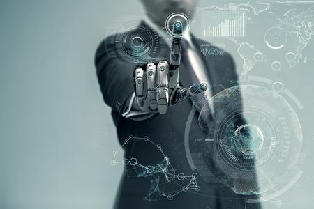 Hombre de negocios con una mano robótica artificial que trabaja en interfaz holográfica virtual. La tecnología del futuro como concepto de diseño.