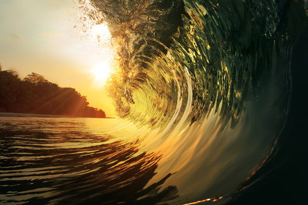 Colorful Ocean Rip Curl at the sunset with the sun inside a wave