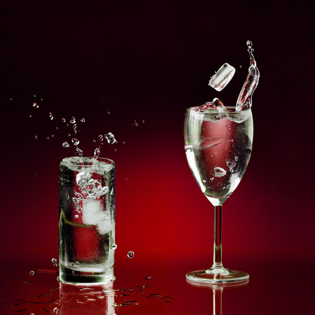 two clear glasses of water standing on wet surface and few pieces of ice dropped with splashes and bubbles Stock Photo