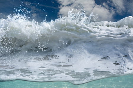 shorebreak: White foam of shorebreak waves in tropical surfing scenery. Rough ocean splashes with water drops.
