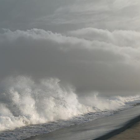 shorebreak: Shorebreak in Los Angeles in Ocean with dark clouds in daylight Stock Photo