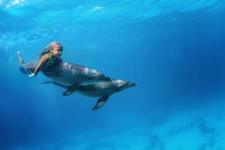 수 중 돌고래의 쌍을 가지고 수영하는 어린 소녀. 해양 생물 스포츠 극단적 인 디자인. 해양 동물과 키즈. 홍 해 다이빙.