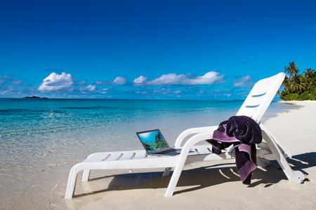 모바일 컴퓨터와 자에 수건 몰디브 열 대 해변. 모바일 사무실로 비치 노트북. 노트북과 함께하는 열대 경치