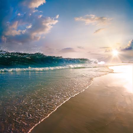shorebreak: beautiful tropical beach with yellow sand, sun reflections, breaking splashing wave, shorebreak under sunset Stock Photo