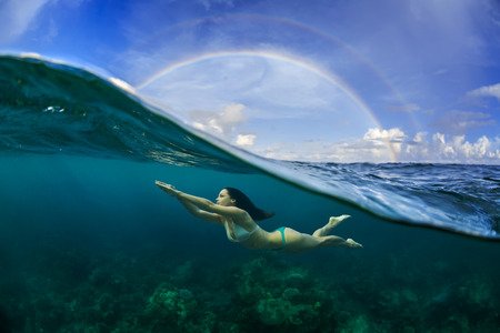 freediver: Underwater Sport Postcard. A freediver floating under water surface in ocean. A rainbow appear on cloudy sky over beautiful seascape Stock Photo