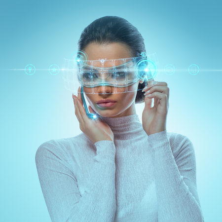 Image of Attractive Businesswoman Wearing Futuristic virtual Glasses Working With Holographic Hud Against Hightech background