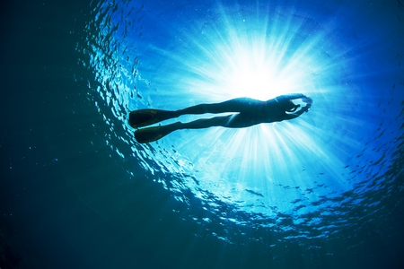 freediving: An ocean Water surface with bright sun underwater behind ripples. Silhouette of female freediver floating through sunbeams. Stock Photo