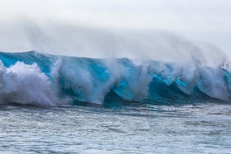 shorebreak: Beautiful Semi-transparent blue ocean wave. Hawaiian translucent Shorebreak at sunset time.