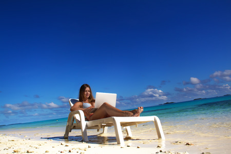 Beautiful girl on tropical beach getting tan and working with laptop Imagens