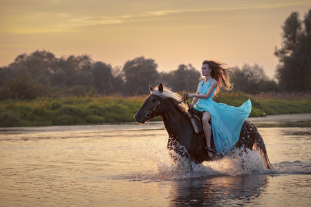 Girl wearing blue dress riding horse in a river on the background of sunset sky and glossy water. Female model on horseback at sunset time, backlit with sunshine with water drops and splashes Фото со стока