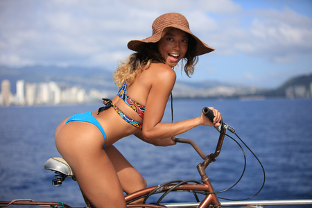 Smiling pacific islander girl weraing bikini sitting on a bike riding bicycle. Seascape with buildings on a beachside. 写真素材