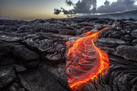 Red Orange vibrant Molten Lava flowing onto grey lavafield and glossy rocky land near hawaiian volcano with vog on background