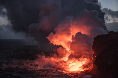 Hot bright lava streams flowing into the ocean making big clouds of steam against sunset sky on background Banque d'images