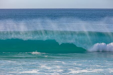 Big blue surfing wave crashing