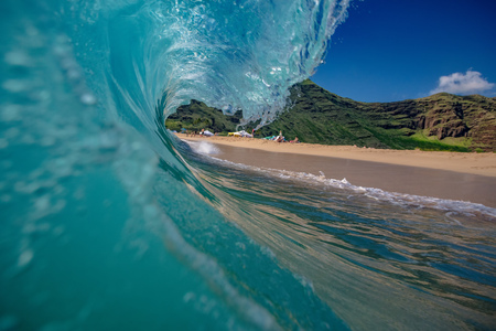 Shorebreak Ocean Wave in a shape of rip curl barrel, ready to crush against sand on a tropical beach. Hawaiian lifestyle